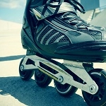 39277047 - closeup of the feet of a young man roller skating with inline skates, with a slight vignette added